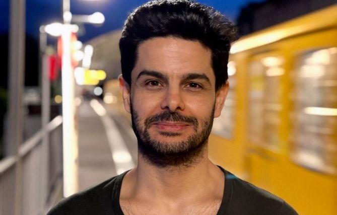 Mamoun Abo Assi, braune Haare und brauner Bart, steht an einer Berliner U-Bahnstation. Hinter ihm fährt eine gelbe U-Bahn vorbei.